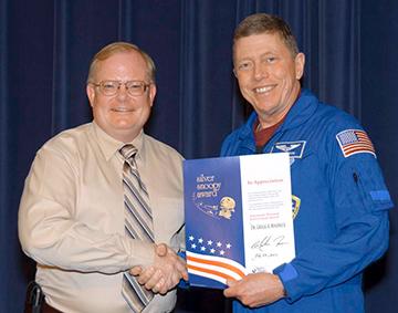 Astronaut Mike Fossum überreicht einen Snoopy-Award. Foto: NASA
